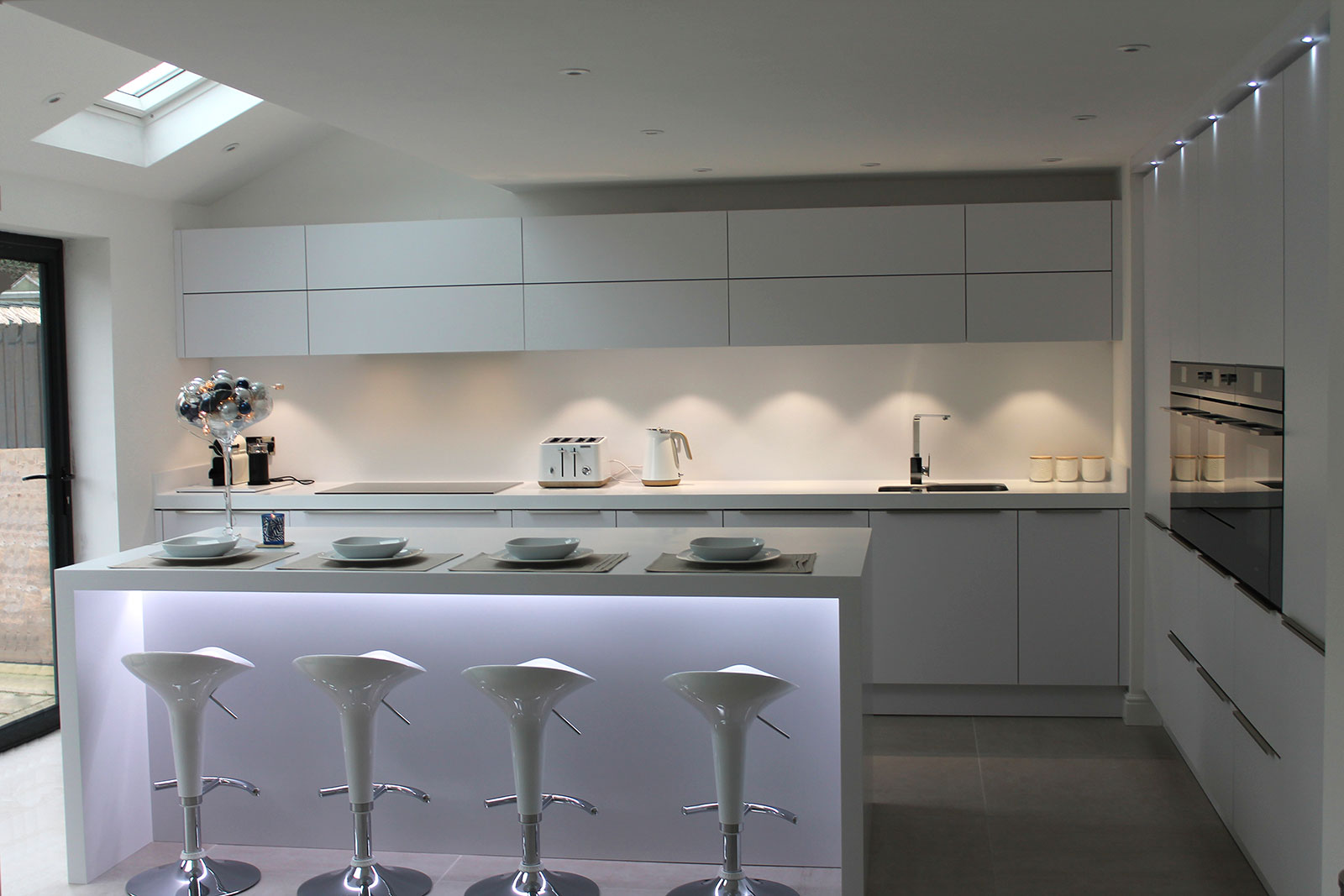 White modern German kitchen with white Corian work surfaces ...
